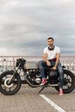 L'uomo brutale si siede sulla motocicletta di abitudine del corridore del caffè immagine stock libera da diritti