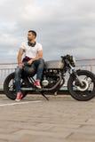 L'uomo brutale si siede sulla motocicletta di abitudine del corridore del caffè immagine stock