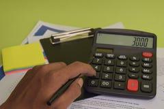 L'uomo calcola il costo e l'analisi del bilancio finanziari Concetto di finanza e di affari della scrivania immagini stock