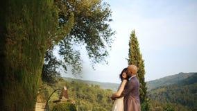 L'uomo calvo abbraccia la sua signora da dietro la condizione sul balcone con grande paesaggio archivi video