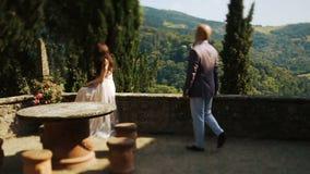 L'uomo calvo cammina a signora sola che si siede sul balcone archivi video