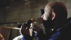 L'uomo calvo con una barba mangia una pagnotta e un caffè delle bevande stock footage