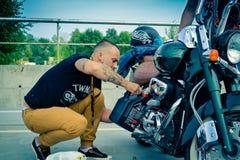 L'uomo cambia l'olio in motocicli Motocicletta Harley Davidson sotto cielo blu Fotografia Stock Libera da Diritti