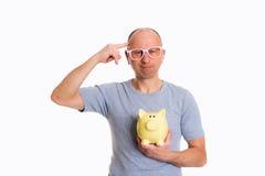 L'uomo in camicia grigia con i vetri rosa ed il porcellino salvadanaio mostrano un uccello Fotografia Stock Libera da Diritti