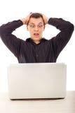 L'uomo in camicia nera che esamina il computer portatile con gli ampi occhi si apre Fotografia Stock