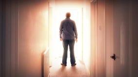 L'uomo cammina attraverso la porta in luce intensa stock footage
