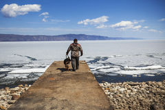 L'uomo cammina con il suo cane vicino al lago in primavera Immagine Stock