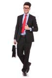 L'uomo cammina con la valigia & tiene il cappotto Immagini Stock Libere da Diritti