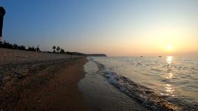 L'uomo cammina lungo la riva del lago Baikal al tramonto stock footage
