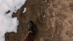 L'uomo cammina lungo la sabbia in molla in anticipo in cui tutta la neve non si è fusa ancora Primo punto di vista della persona video d archivio
