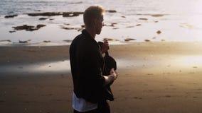 L'uomo cammina lungo la spiaggia di sabbia nera, fa la vibrazione contro luce dorata del tramonto, movimento lento, chiarore dell archivi video