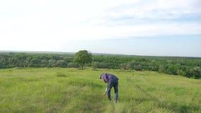 L'uomo cammina in natura attraverso il campo il viaggiatore va nello stile di vita turistico dell'albero solo della natura video d archivio