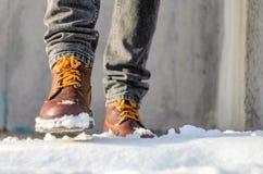 L'uomo cammina nella via della neve Piedi calzati negli stivali marroni di inverno Immagine Stock