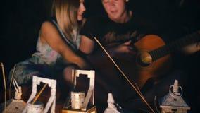 L'uomo canta una canzone con una chitarra alla sua amica - la notte in un campo con le lanterne della candela video d archivio