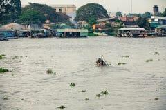 L'uomo in cappello conico asiatico sta galleggiando giù il Mekong, Vietnam Fotografie Stock