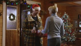 L'uomo in cappello di Santa dà un regalo di Natale al suo grlfriend e lo bacia e prende alla casa archivi video