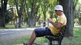 L'uomo in cappello ed occhiali da sole sta utilizzando lo smartphone in parco sul banco Uomo facendo uso dello smartphone mentre  stock footage