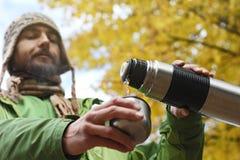 L'uomo in cappello tricottato, con il sorriso versa una bevanda calda - tè o caffè fotografia stock