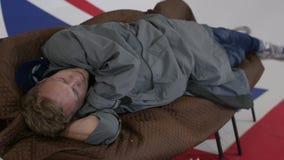 L'uomo in cappotto grigio lungo si trova sul sofà e graffia il suo indietro nella sala con la bandiera BRITANNICA archivi video