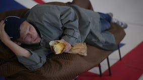 L'uomo in cappuccio blu e cappotto grigio si trova sul sofà e mangia il pane nella sala con la bandiera BRITANNICA video d archivio