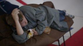 L'uomo in cappuccio blu e cappotto grigio si trova sul sofà e mangia la pagnotta nella sala con la bandiera BRITANNICA video d archivio