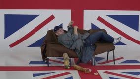 L'uomo in cappuccio e cappotto grigio si trova sul sofà e gira intorno nella sala con la bandiera BRITANNICA archivi video