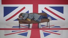 L'uomo in cappuccio e cappotto grigio si trova sul sofà e graffia nella sala con la bandiera BRITANNICA video d archivio