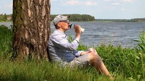 L'uomo in cappuccio si siede sotto un albero sulla riva dell'acqua delle bevande e del lago archivi video
