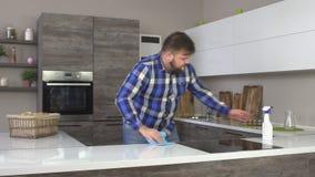 L'uomo casalingo allegro in una camicia di plaid lava una tavola nella cucina, l'interno moderno, lento-Mo, dell'interno stock footage