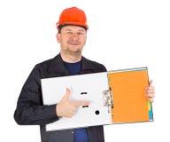 L'uomo in casco rosso mostra la cartella di carta aperta Immagine Stock