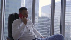 L'uomo castana attraente in camicia bianca parla sullo smartphone in ufficio moderno video d archivio