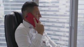 L'uomo castana attraente in camicia bianca parla sullo smartphone in ufficio moderno stock footage