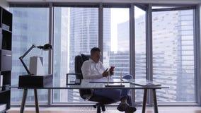 L'uomo castana attraente in camicia bianca si siede dietro lo scrittorio di vetro in ufficio moderno video d archivio