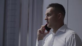 L'uomo castana sveglio in camicia bianca parla sullo smartphone vicino alla finestra in ufficio stock footage