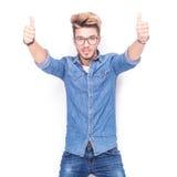 L'uomo casuale felice che fa l'approvazione sfoglia sul segno della mano Immagine Stock