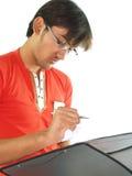 L'uomo cattura le note in dispositivo di piegatura Fotografia Stock Libera da Diritti