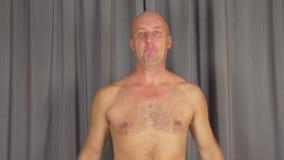 L'uomo caucasico adulto si scalda i muscoli delle spalle Giri le mani, gira i braccia video d archivio