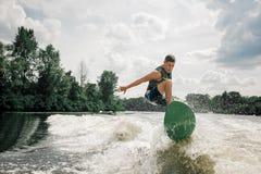 L'uomo caucasico guida le onde dal wakeboard alla moda fotografie stock libere da diritti
