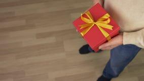 L'uomo caucasico in maglione beige sta tenendo un contenitore di regalo in mani Punto di vista superiore dell'uomo in maglione be video d archivio