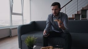 L'uomo caucasico serio nell'usura convenzionale sta sedendosi allo strato ed alla TV di sorveglianza video d archivio