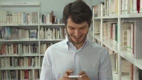 L'uomo cerca un libro alla biblioteca immagine stock