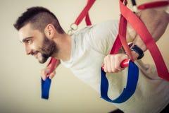 L'uomo che adatto fare spinge aumenta le armi di addestramento con le cinghie di forma fisica Immagini Stock