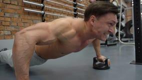 L'uomo che bello di forma fisica fare spinge aumenta in palestra archivi video