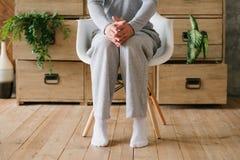 L'uomo che di dubbio di mattina i pigiami si siedono la sedia ha camminato in punta di piedi immagini stock libere da diritti