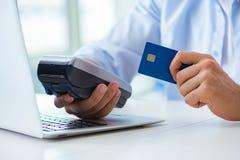 L'uomo che elabora transazione della carta di credito con il terminale di posizione Immagini Stock