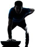 L'uomo che esercita il bosu spinge aumenta la posizione di forma fisica Immagini Stock Libere da Diritti