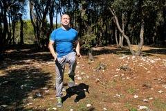 L'uomo che fa l'esercizio sul posto funzionato allenamento in abiti sportivi d'uso dello sportivo bello della foresta sta eseguen Fotografia Stock