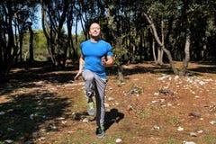 L'uomo che fa l'esercizio sul posto funzionato allenamento in abiti sportivi d'uso dello sportivo bello della foresta sta eseguen Fotografia Stock Libera da Diritti