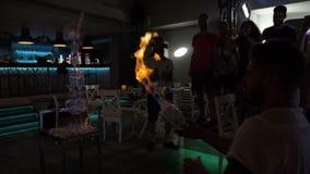 L'uomo che fa i trucchi che spruzzano la fiamma della vodka dalla bottiglia mette sulla pila del fuoco di vetri stock footage