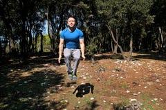 L'uomo che fa il salto di allenamento su nell'esercizio di aria in abiti sportivi d'uso dello sportivo bello della foresta sta sa Immagini Stock